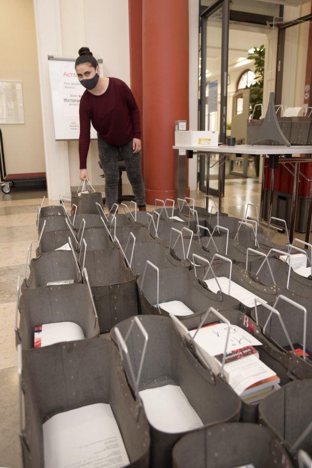 Özlem Özbag gibtTaschen voller zuvor bestellter Medien an die Bibliotheksbenutzer aus.